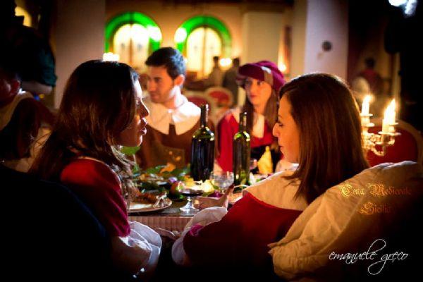 Due donne medievali fanno conversazione a tavola