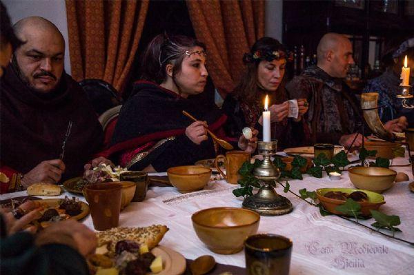 Uomini e donne seduti a tavola in epoca medievale